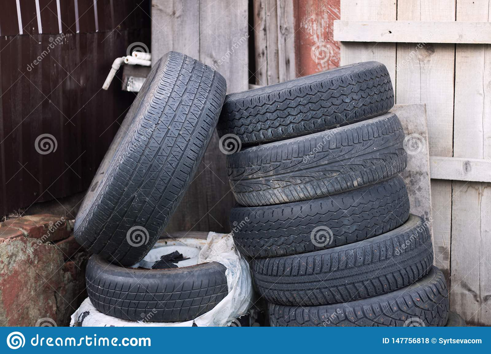 Old rubber tires randomly lie near an abandoned wooden house