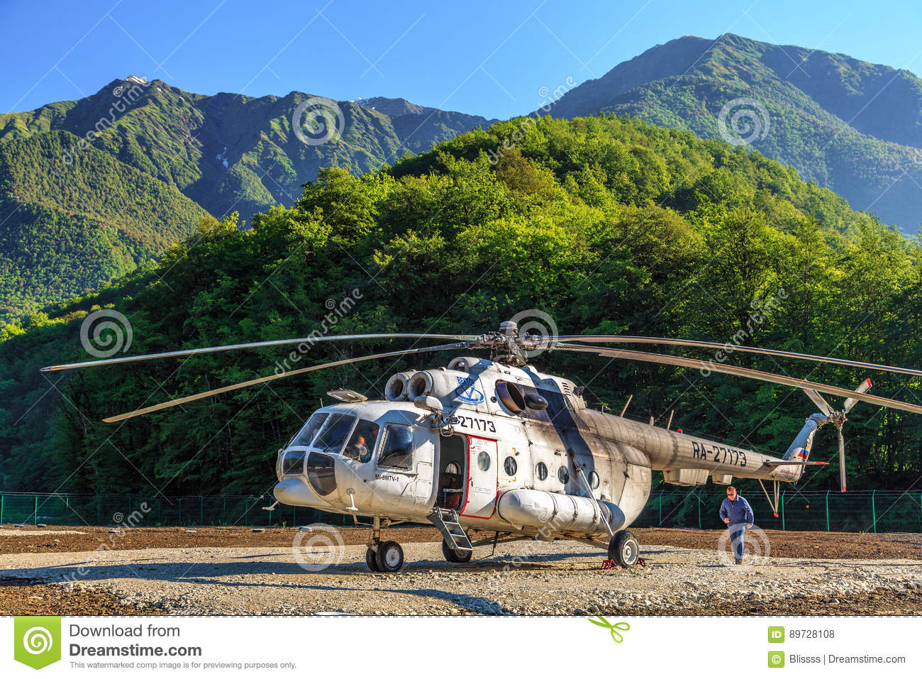 Old Russian helicopter MI-8 stands on landing pad in green Caucasus mountain forest and ready for flight