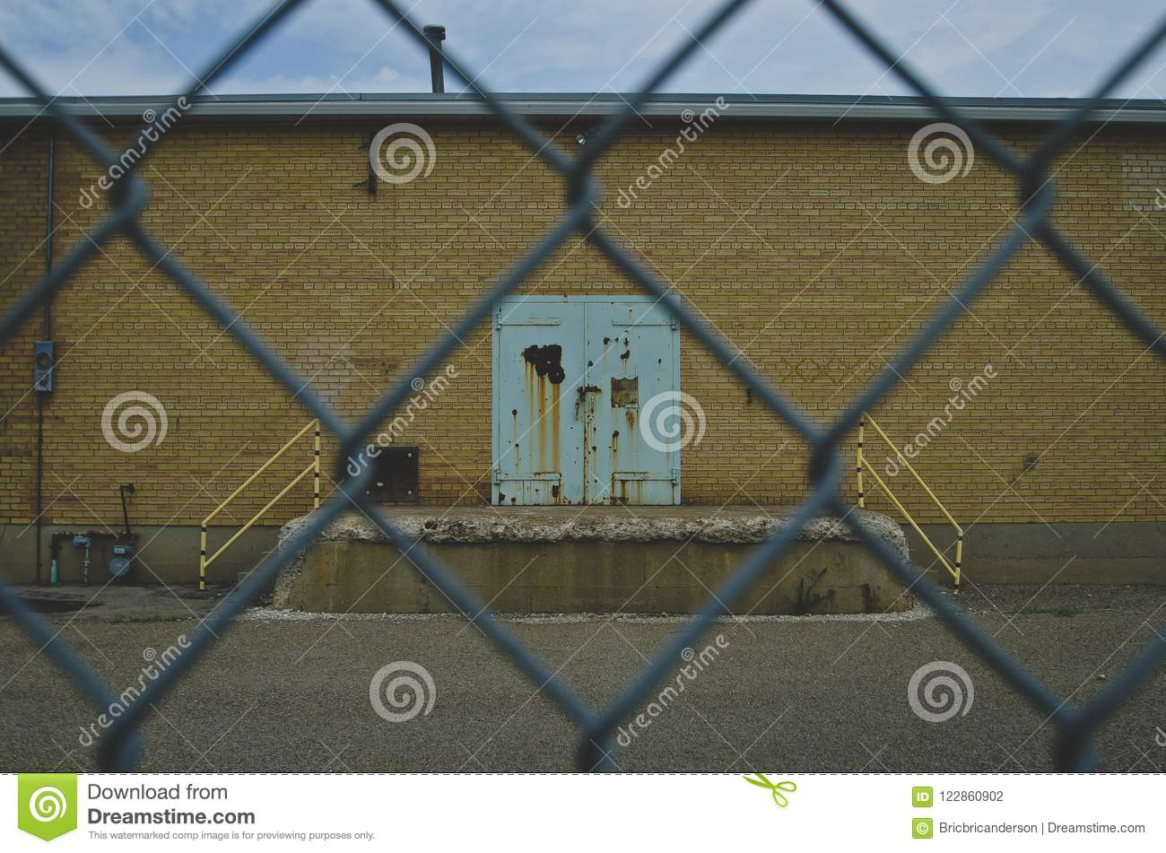 A old rust and teal colored door on the old factory wall through the fence
