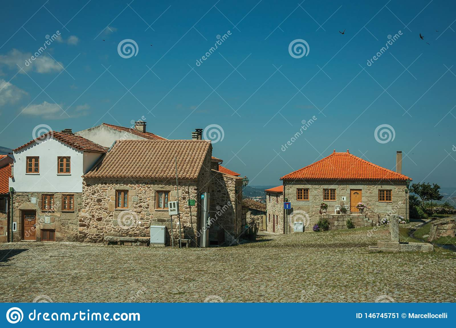 Old rustic houses made of stone in front of square