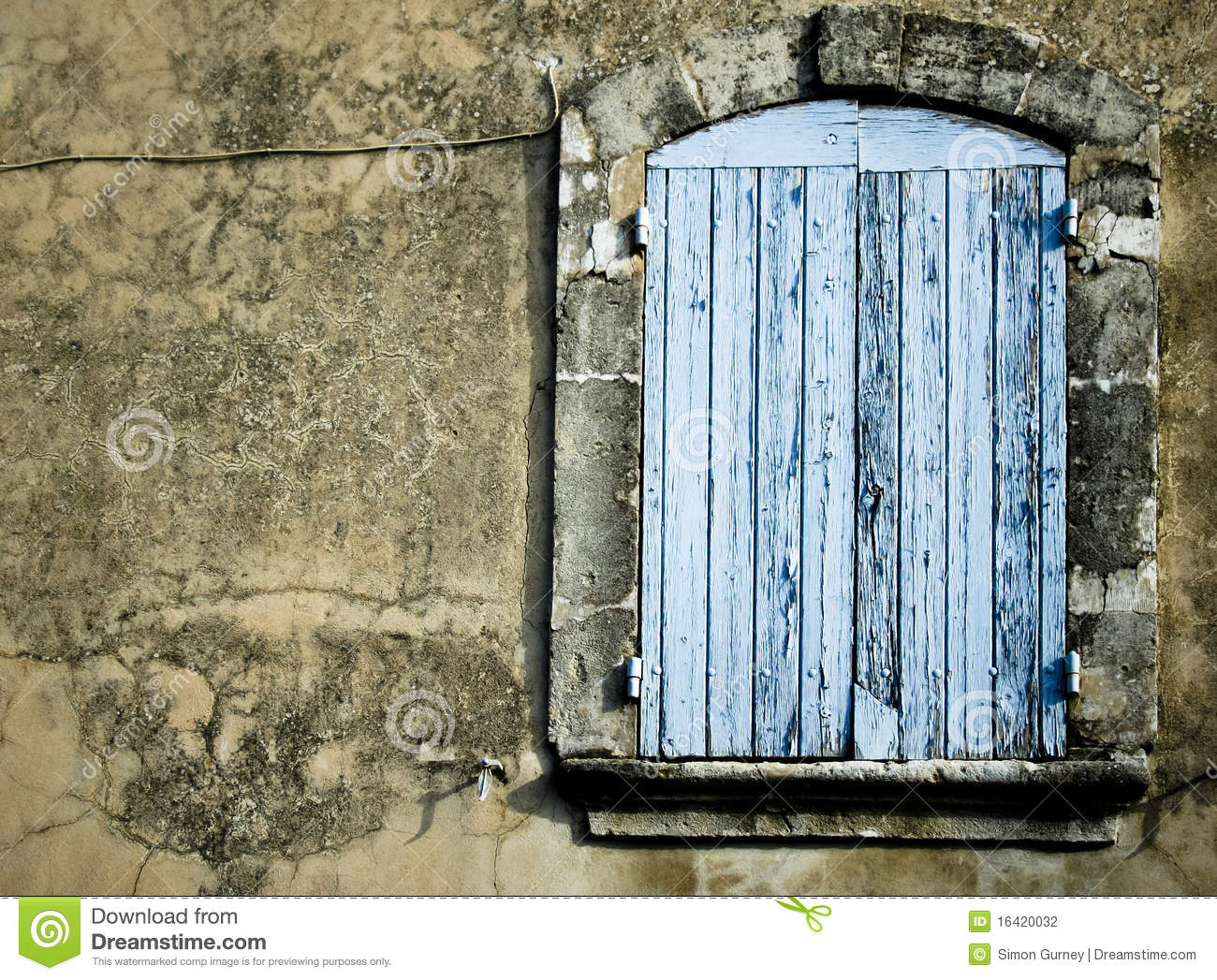 Weathered old blue wooden window on side of house in provence france.