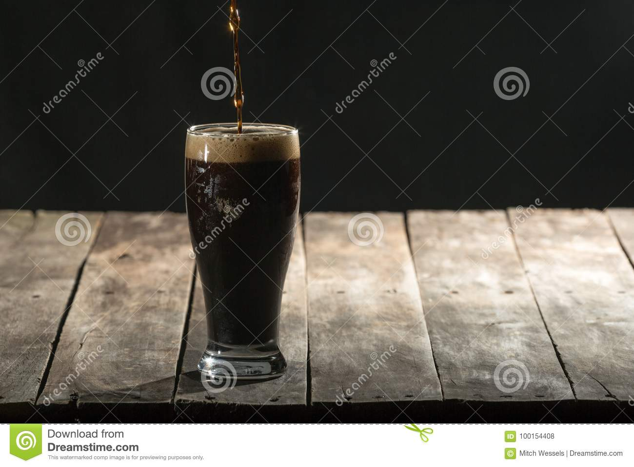 Wood table with black background and craft beer