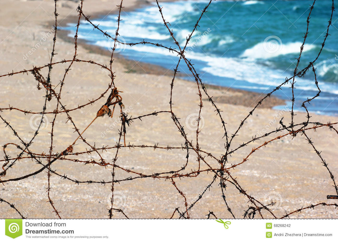 Old rusty barbed wire fence on a beach stock photo image