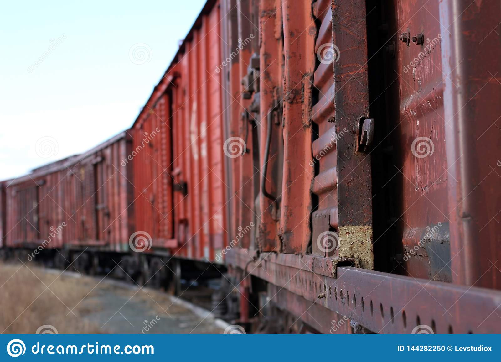 Old rusty freight train stands on rails