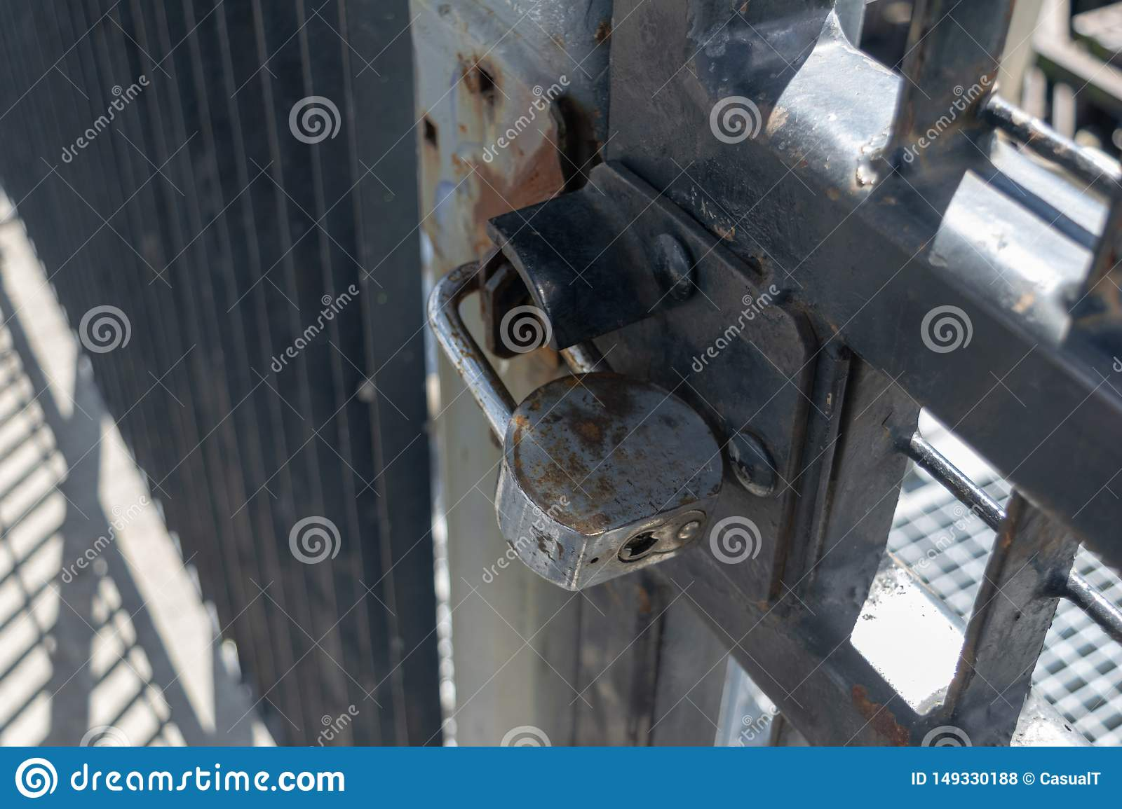 Old and rusty heavy duty pad lock securing aan iron gate, closeup
