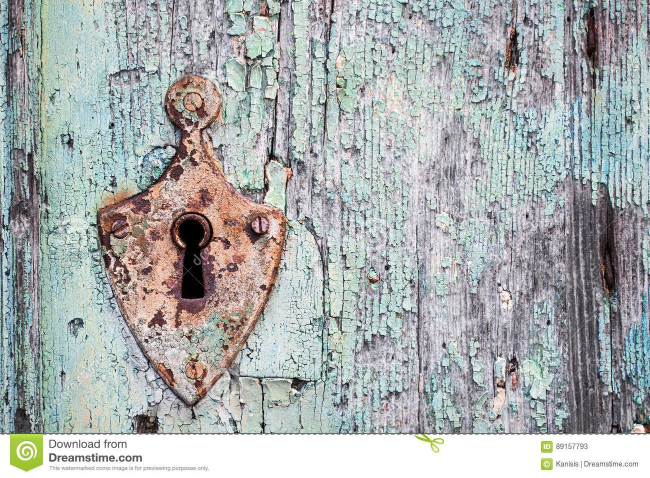 Old rusty metal lock and keyhole on a old turquoise wooden door