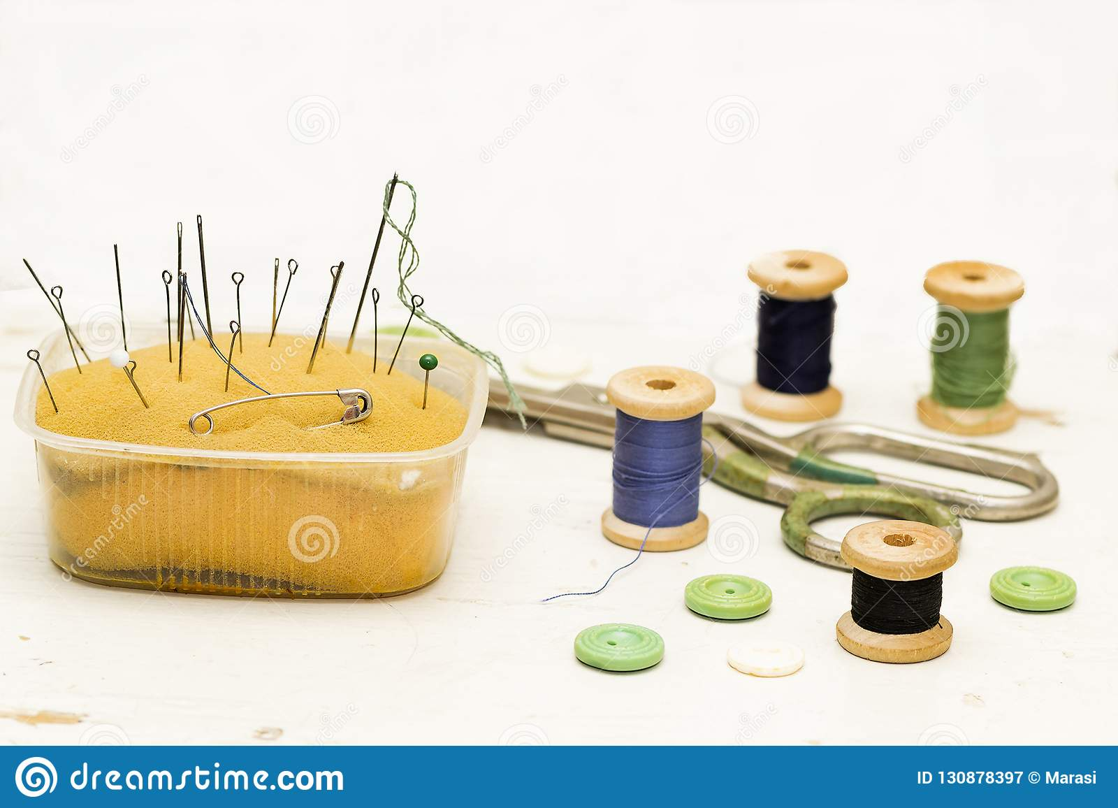 Old rusty, metal needles, pins, scissors and wooden spools of th
