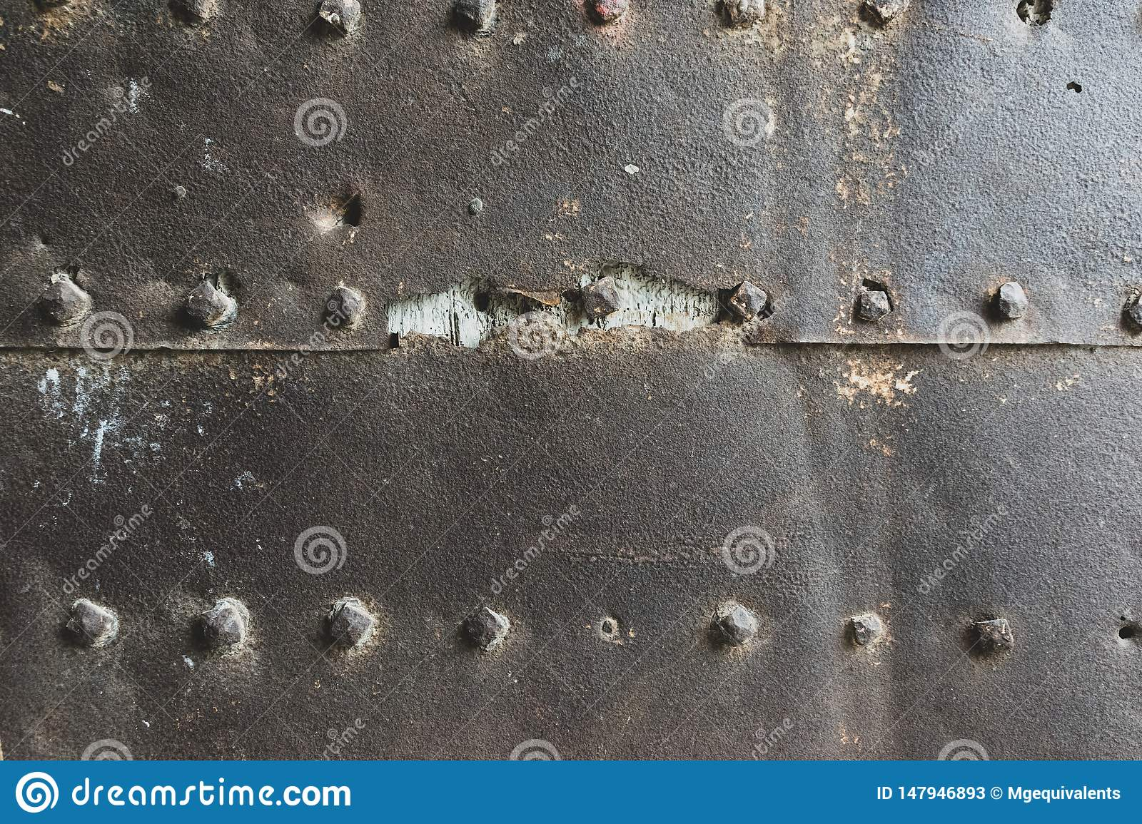 Old and rusty metal wall surface with big rivets