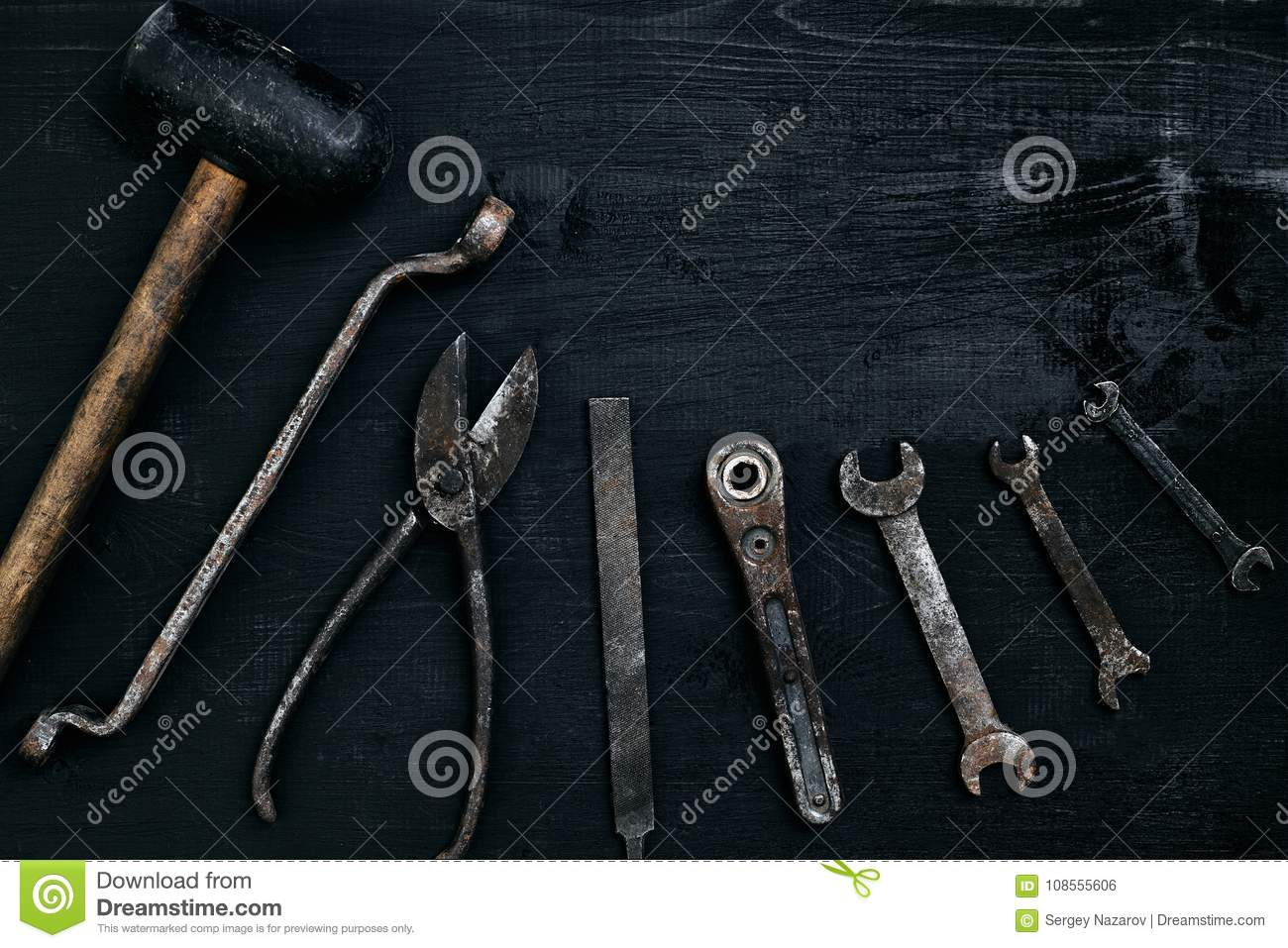 Old, rusty tools lying on a black wooden table. Hammer, chisel, metal scissors, wrench.