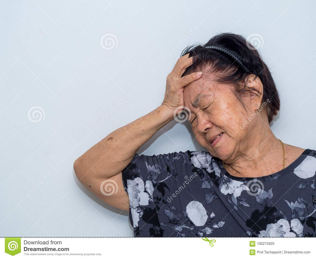 Old senior woman suffering and covering face with hands in headache and deep depression. emotional disorder, grief and desperation