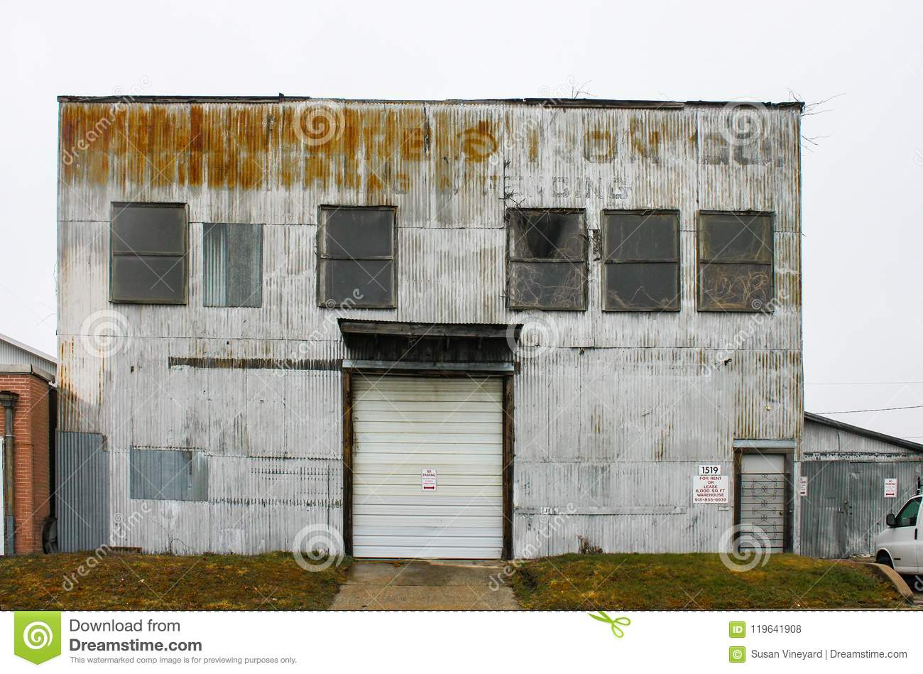 Old sheet metal industrial building with faded lettering and plants growing in windows and out of roof and for rent sign Tulsa OK