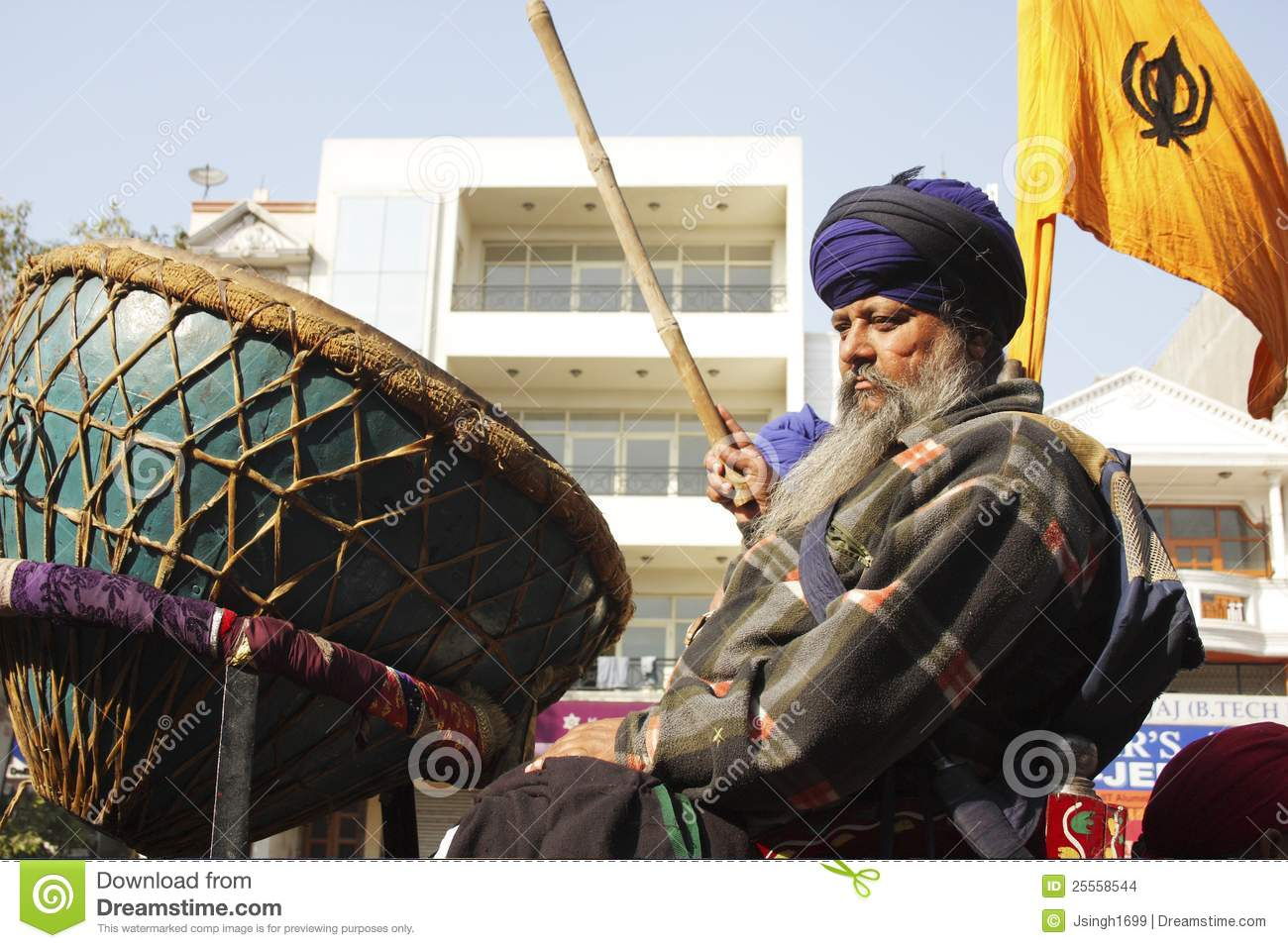 An old sikh gentleman beating a huge drum Nagara