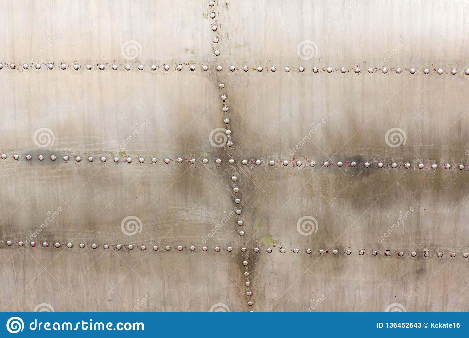 Old silver metal surface of the aircraft fuselage with rivets. Iron plate,steel sheet texture,pattern and background.