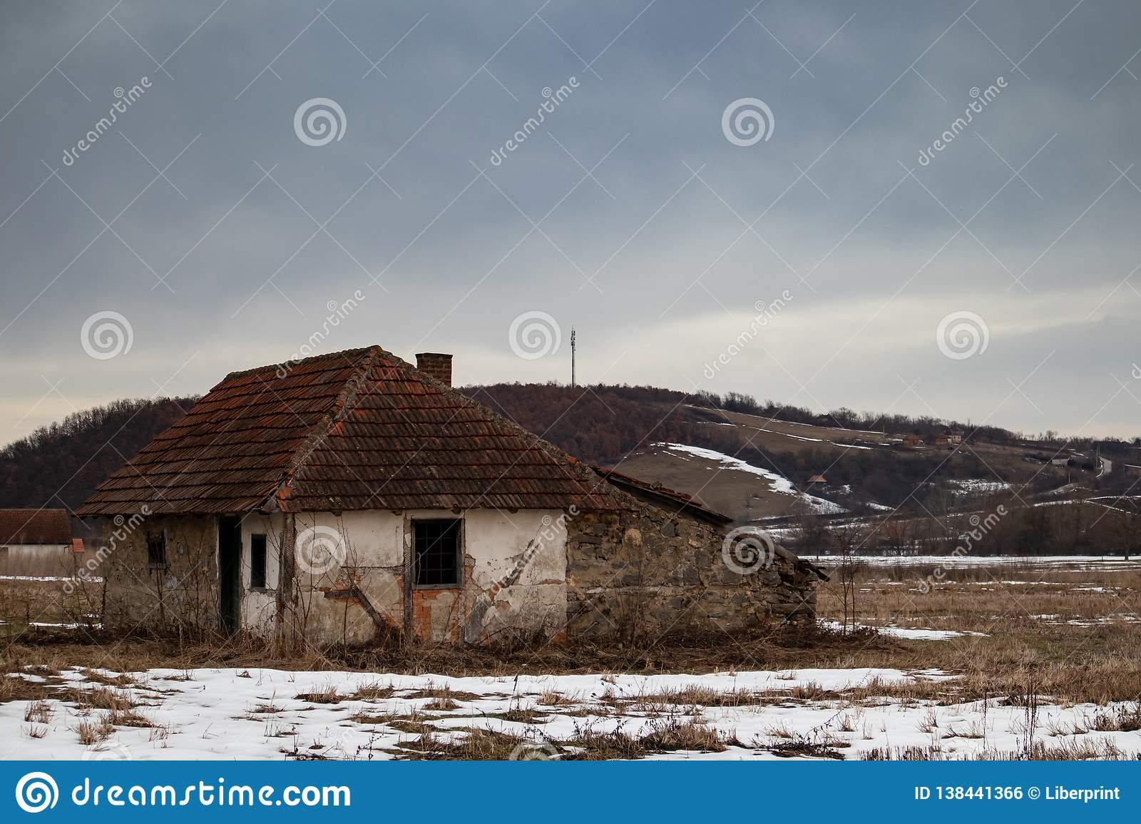 Old small abandoned house on meadow