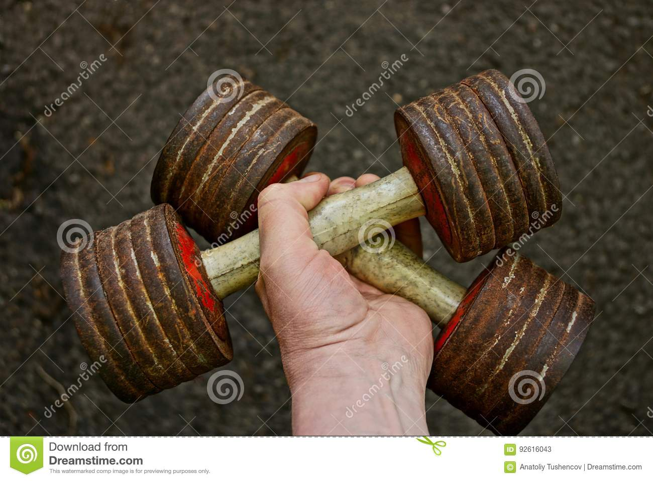 Old sports dumbbells in hand