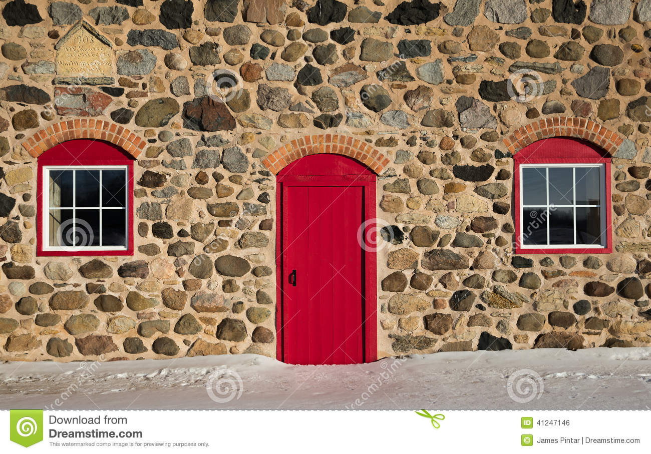 Old Stone Barn With Bright Red Door And Two Windows Stock