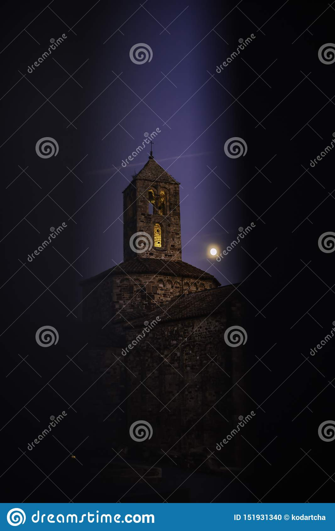 Old stone church on an evening with the moon close to the bell tower seen through gate