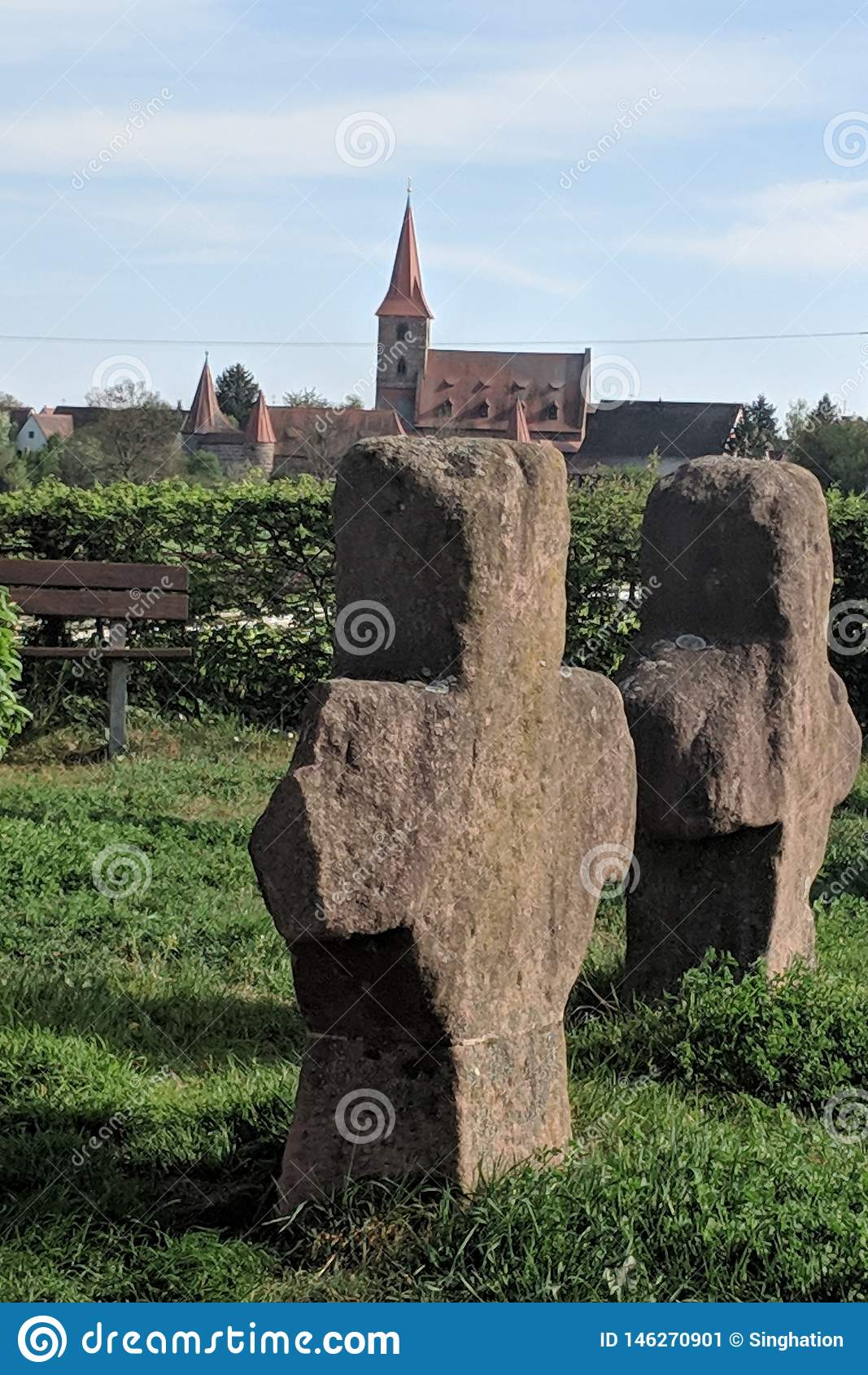 Old stone crosses and in background church of Kraftshof