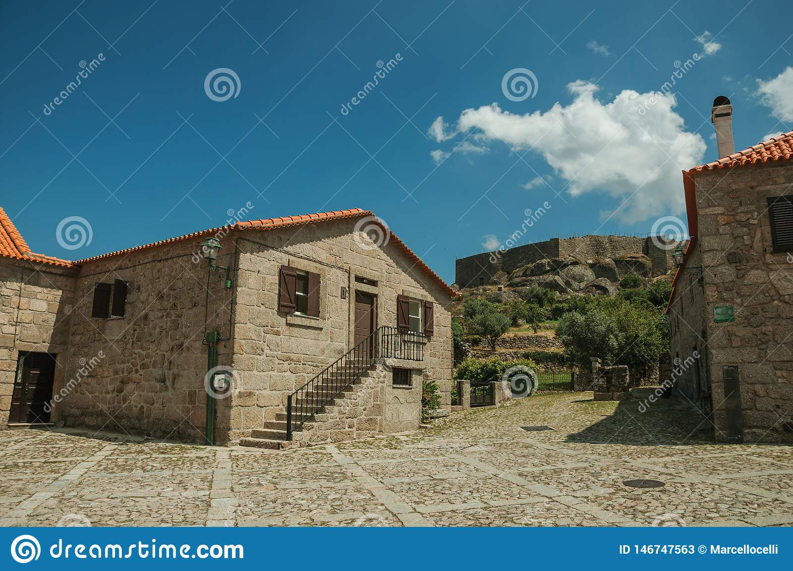 Old stone house on cobblestone alley and castle wall