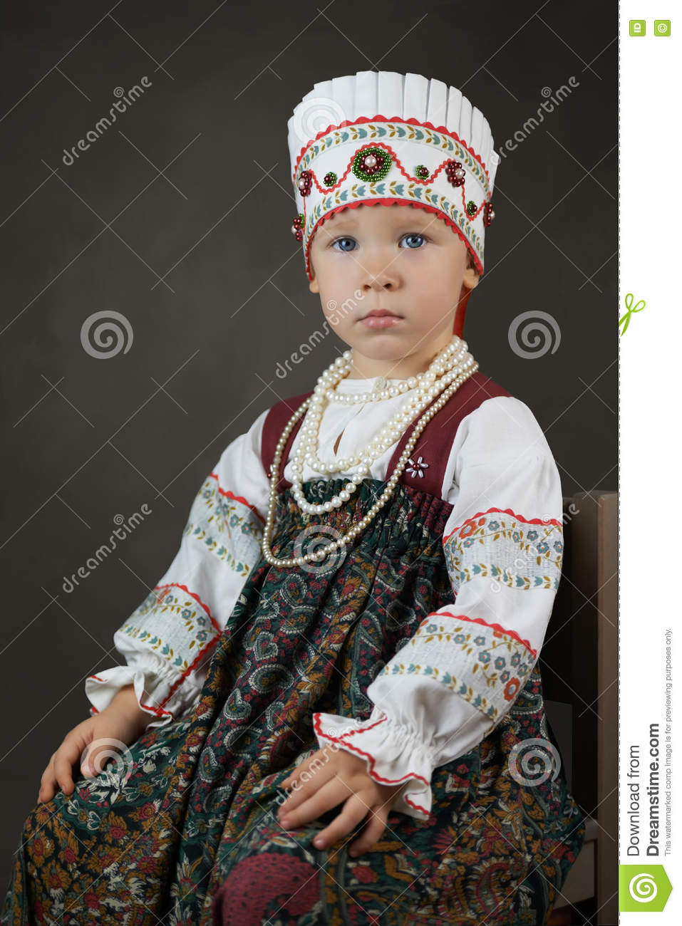 Old style portrait of the little girl in the traditional russian shirt, sarafan and kokoshnik