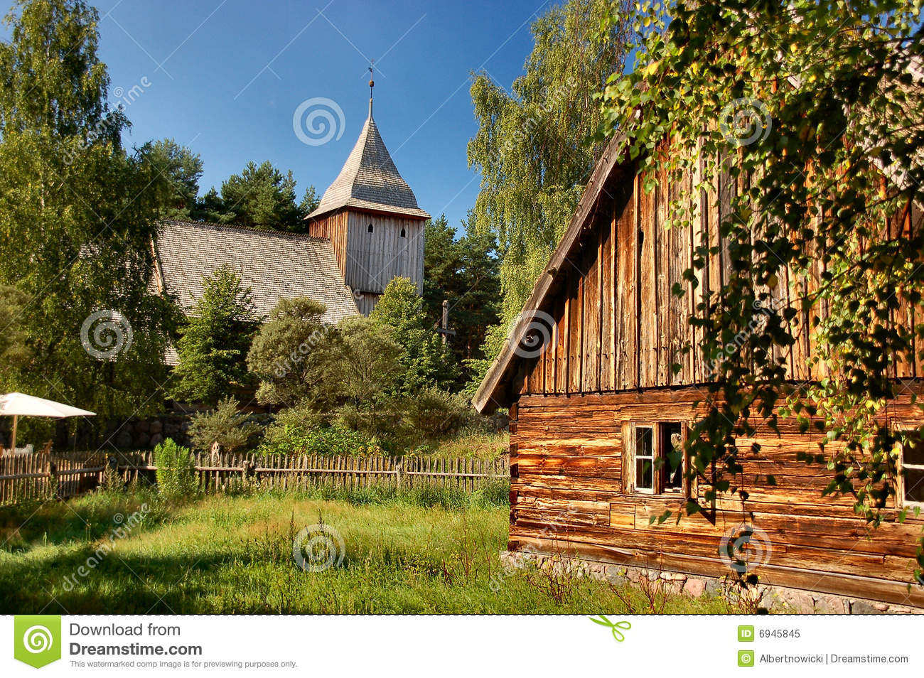 Old stylish cottage with wooden church in the back
