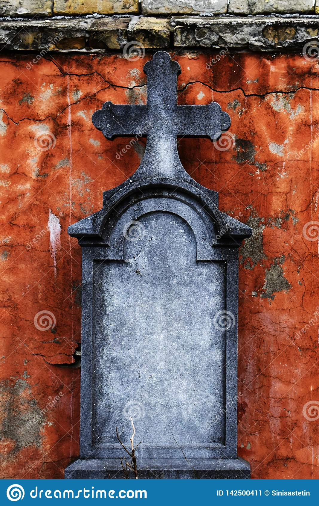 Old gravestone with cross in front of crumbling facade