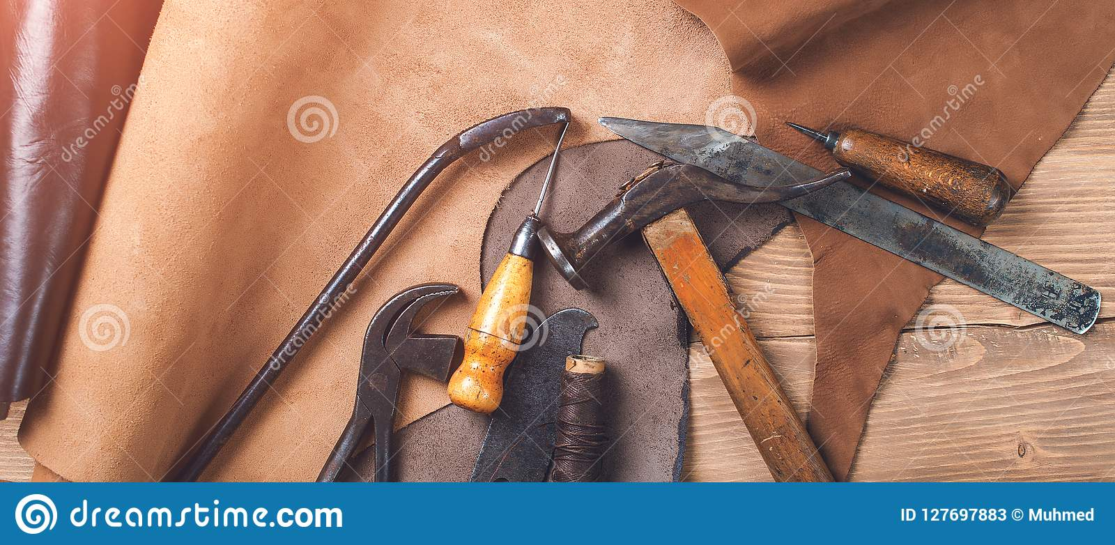 Old tools and leather at cobbler workplace. Shoemaker`s work desk. Flat lay, top view. Set of leather craft tools on wooden backg