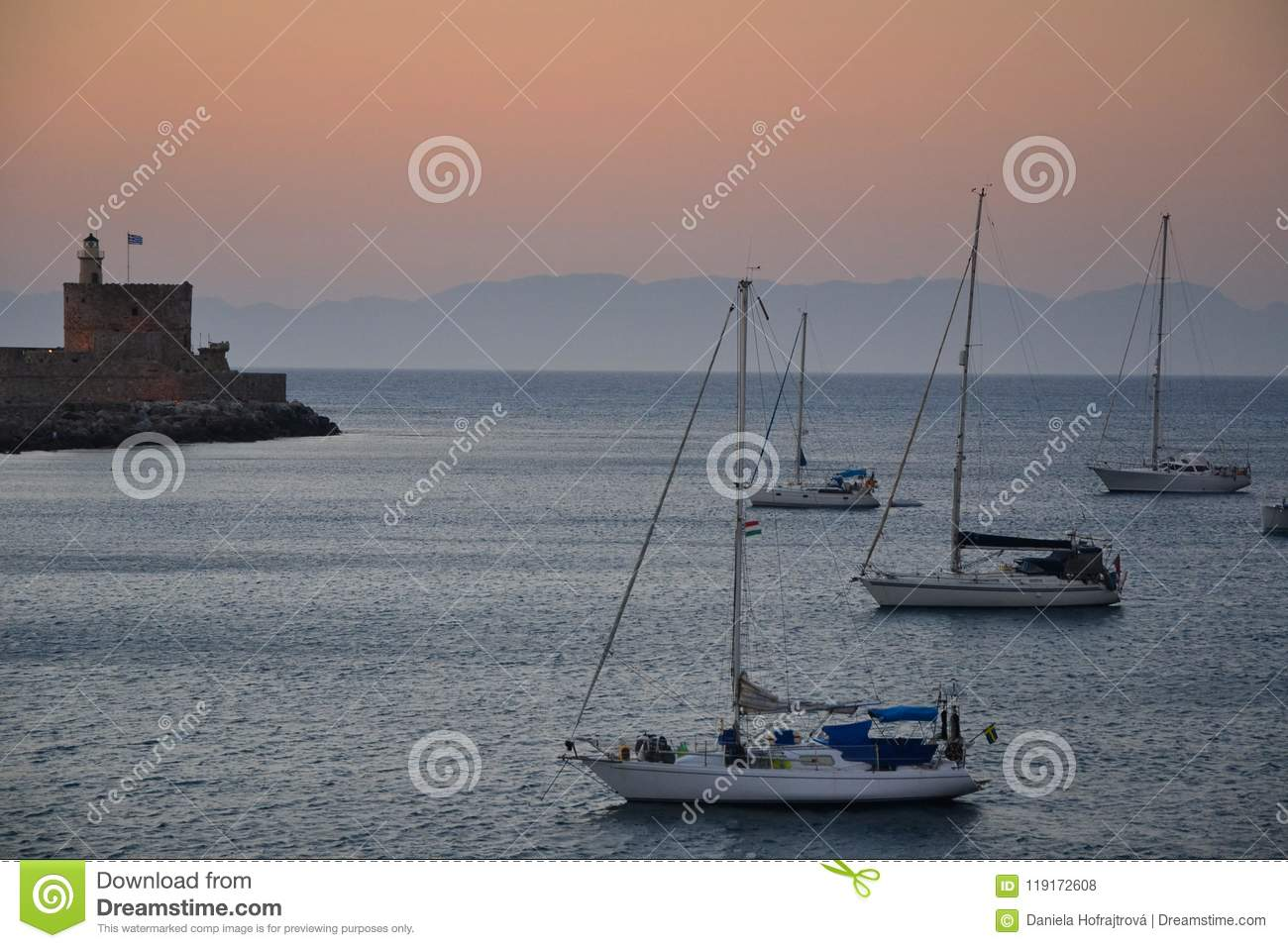 Old Town of Rhodos while pink sunset, calm sea, greek monument and harbour view. Warm colours, foggy background. Rhodos, Greece, E