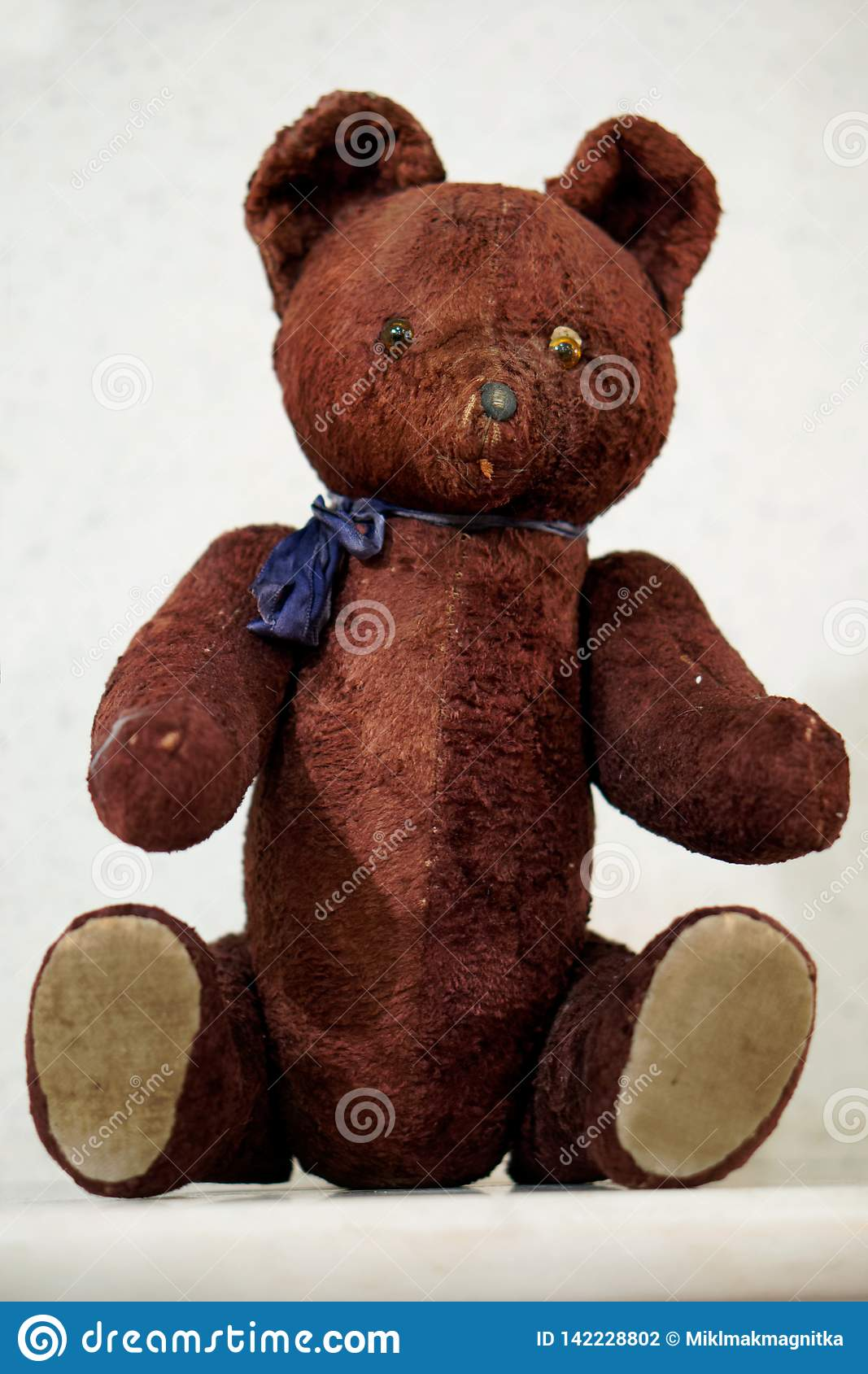 Old toy - a vintage plush brown bear sits on the mantel