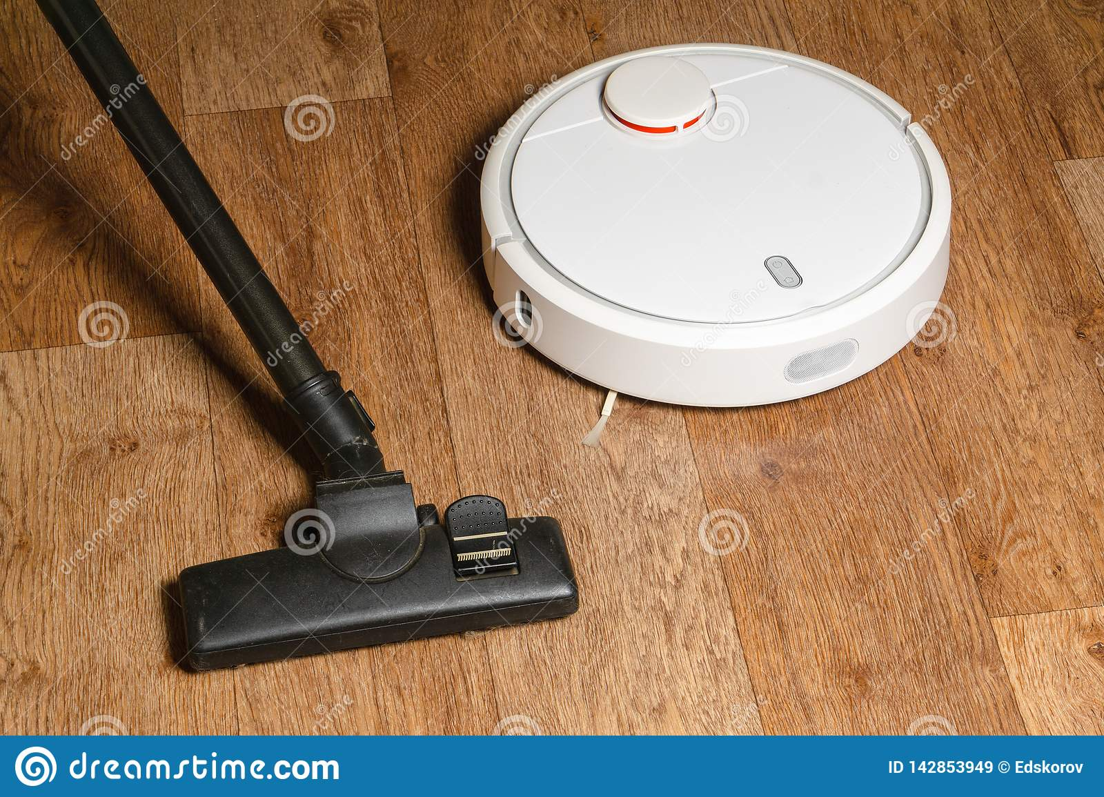 Old vacuum cleaner and new robot vacuum cleaner on the floor