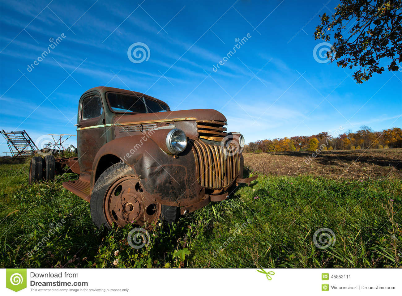 Landscape scene of an old vintage farm truck. In the background is a ...