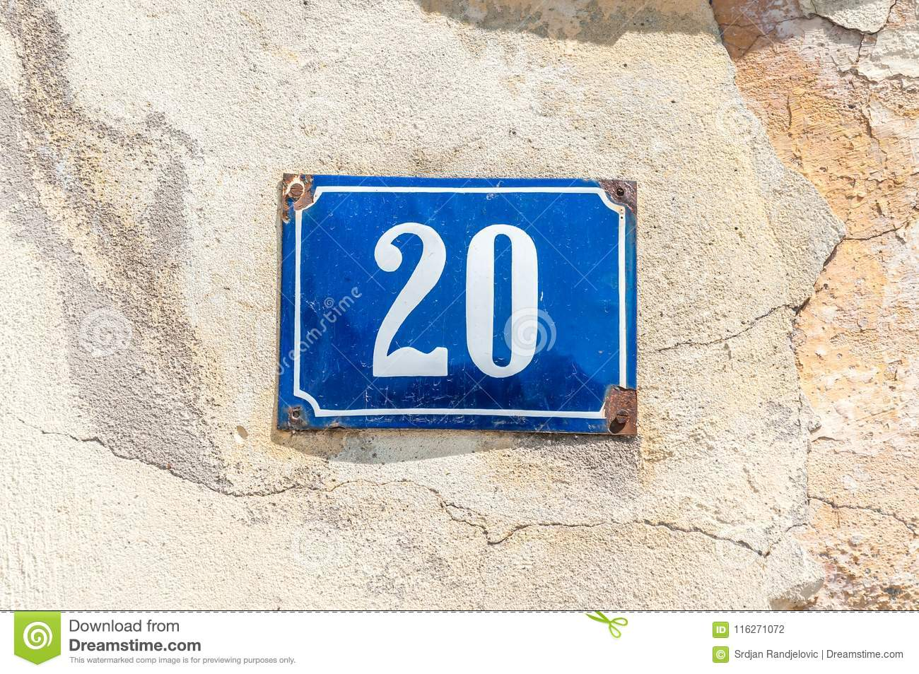 Old vintage house address metal number 20 twenty on the plaster facade of abandoned home exterior wall on the street side