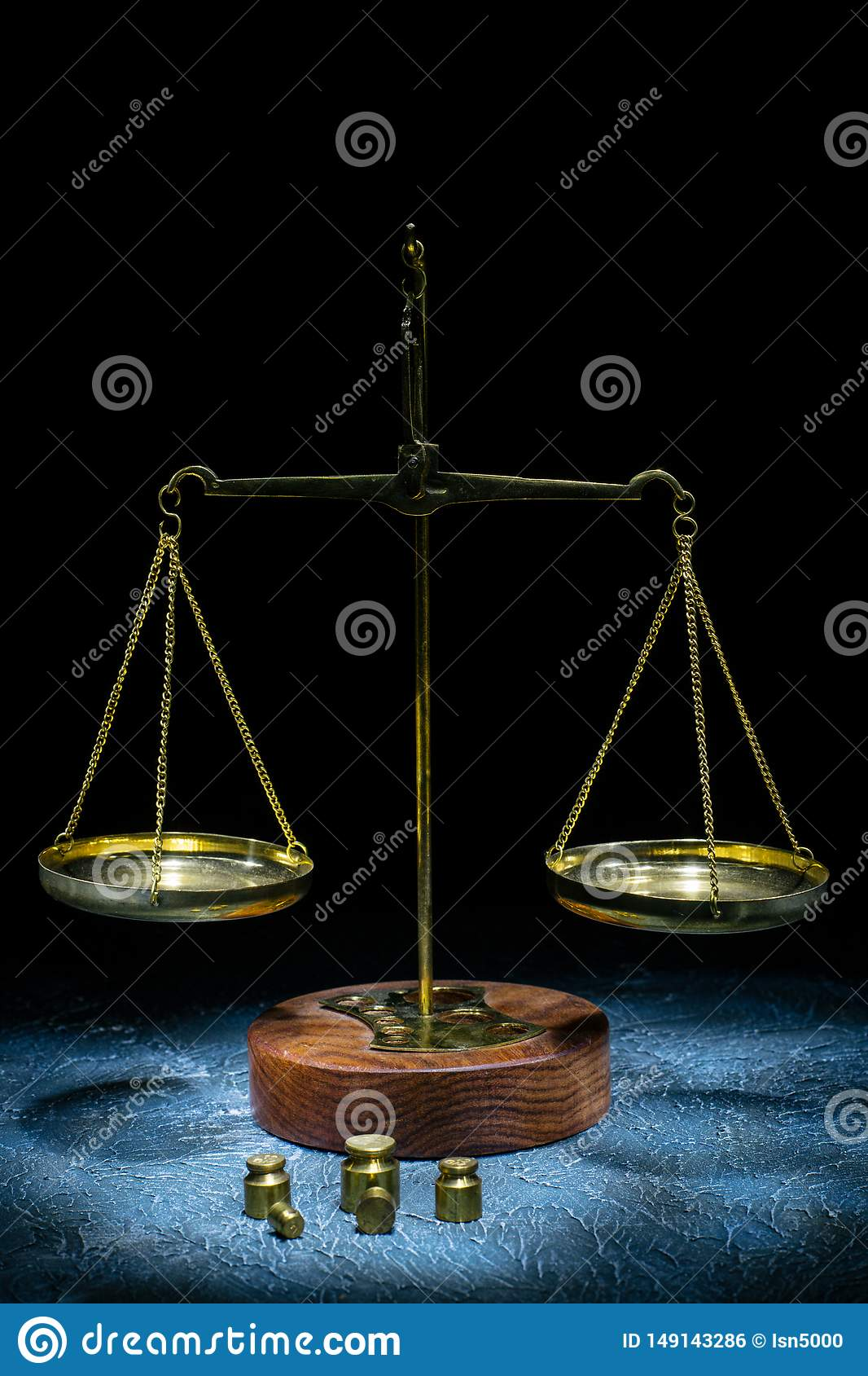 Old vintage scales of justice with weights stand on a stone background. Picture taken with a light brush