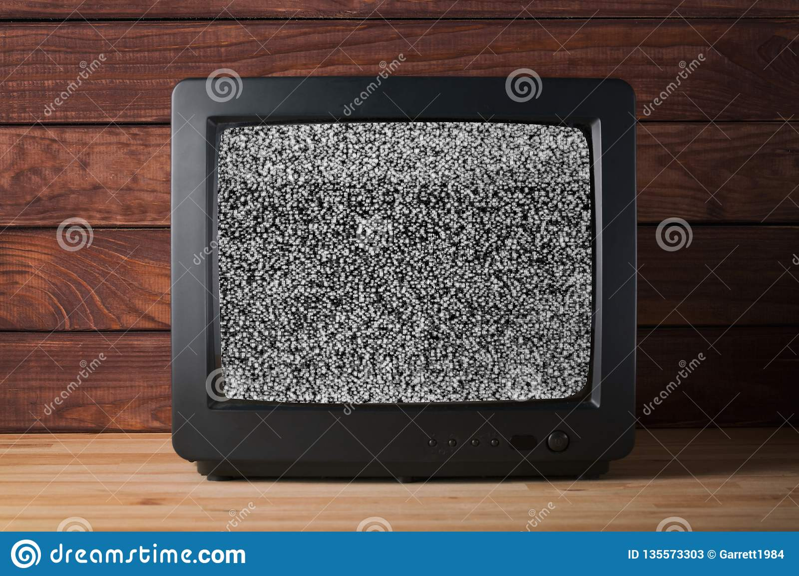 Old vintage TV set televisor on wooden table againt dark wooden wall background with no signal television grainy noise effect on