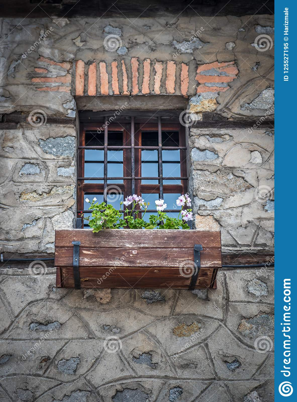 Old Vintage Window With Iron Bars And Flowers In The Pot