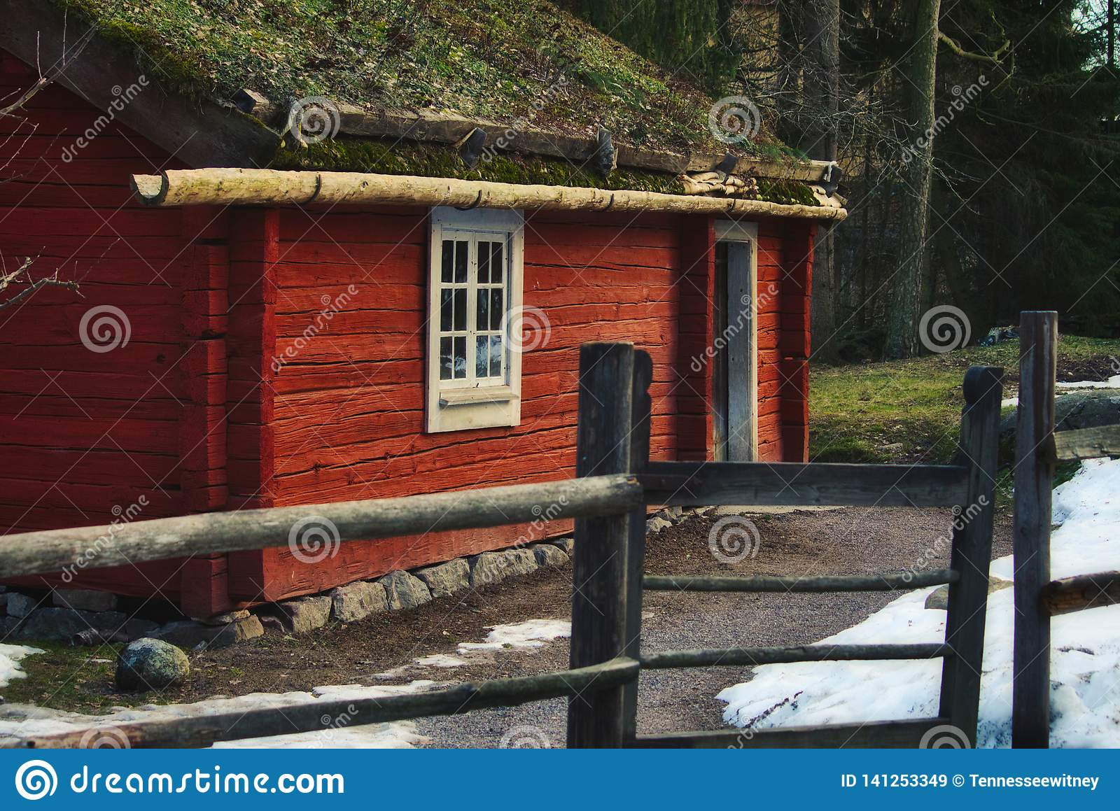Old quaint vintage wood cabin in the forest painted red