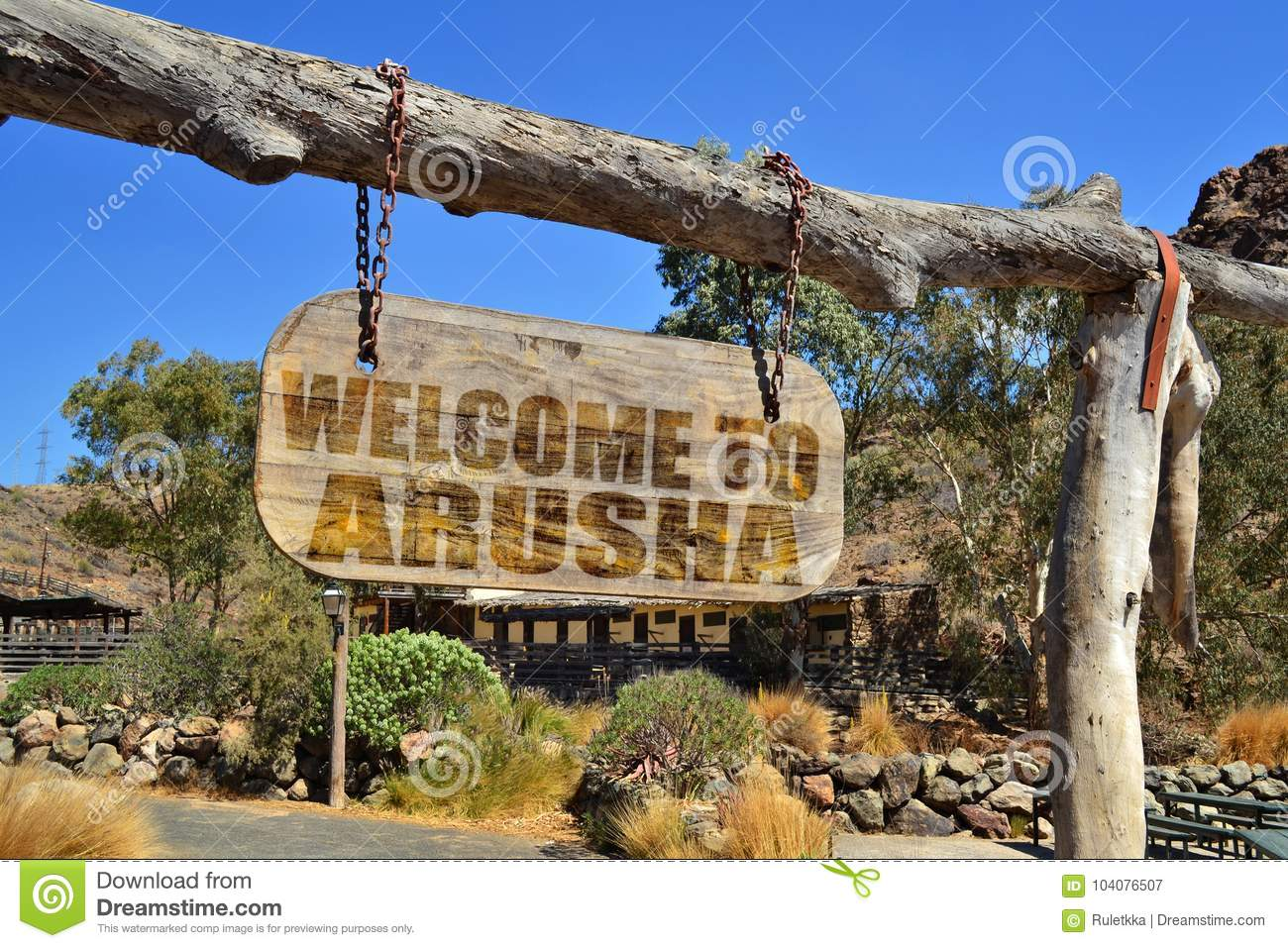 Vintage wood signboard with text welcome to Arusha. hanging on a branch