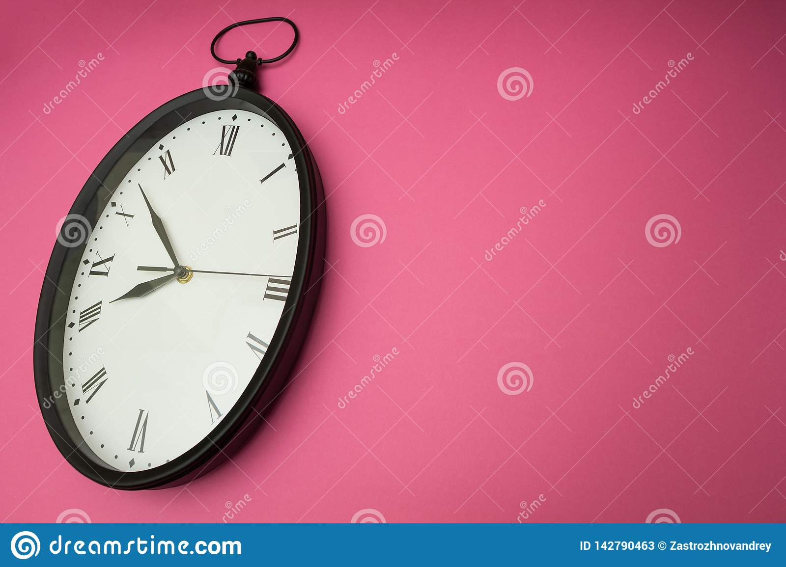 Old wall clock on a pink background