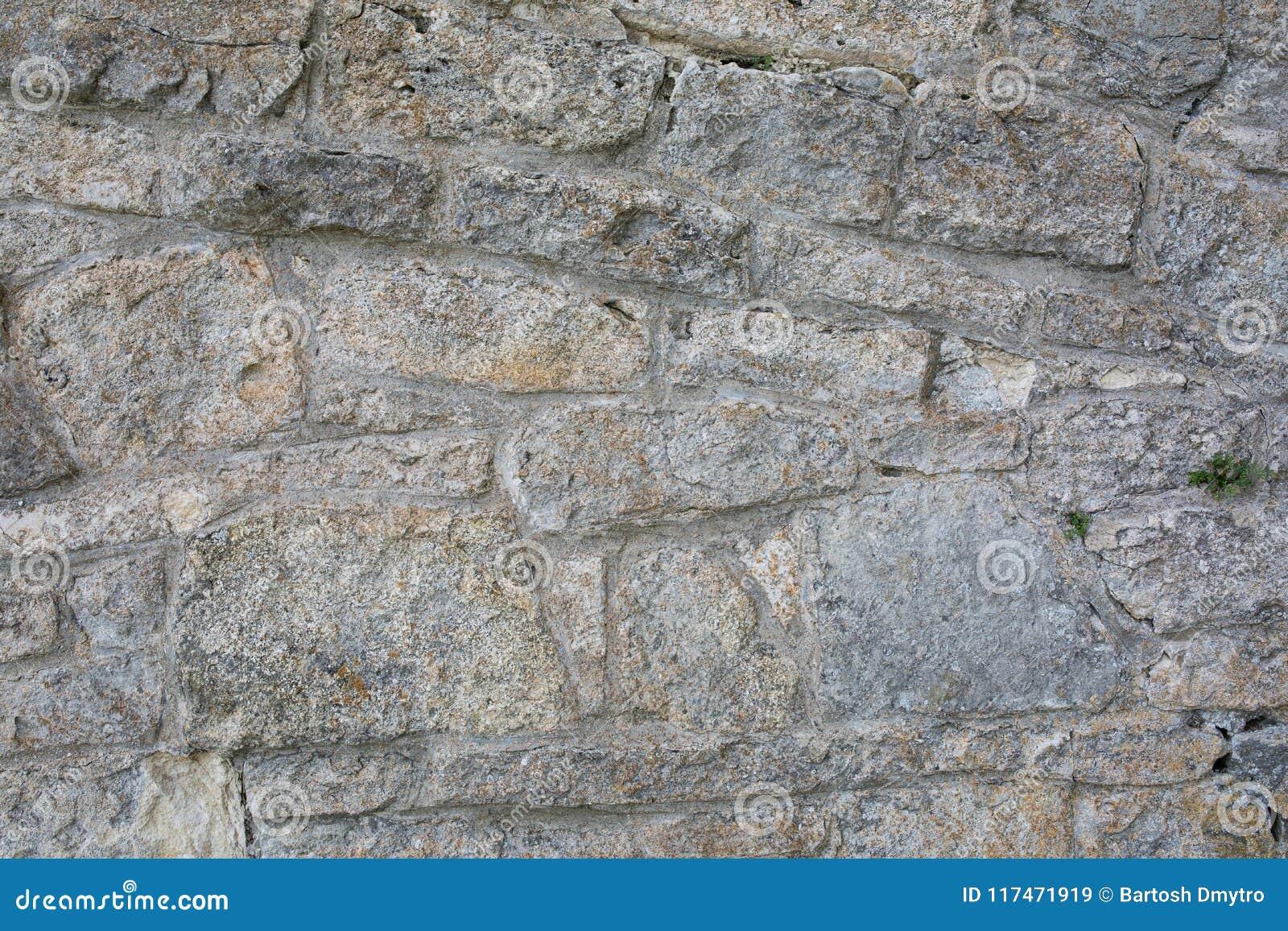 Old wall made of big stones and broken bricks