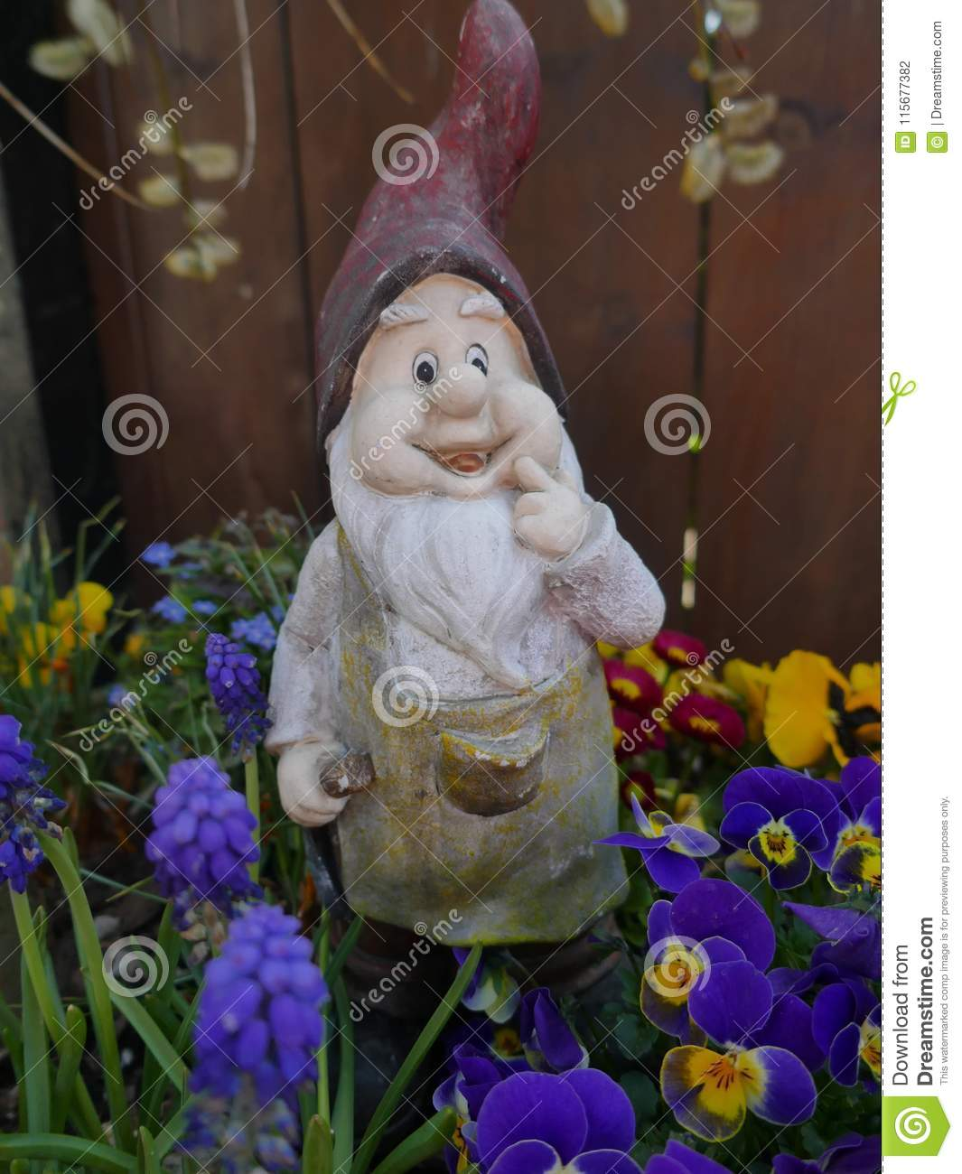 Charming Old Weathered Garden Gnome Stands In A Flowerbed