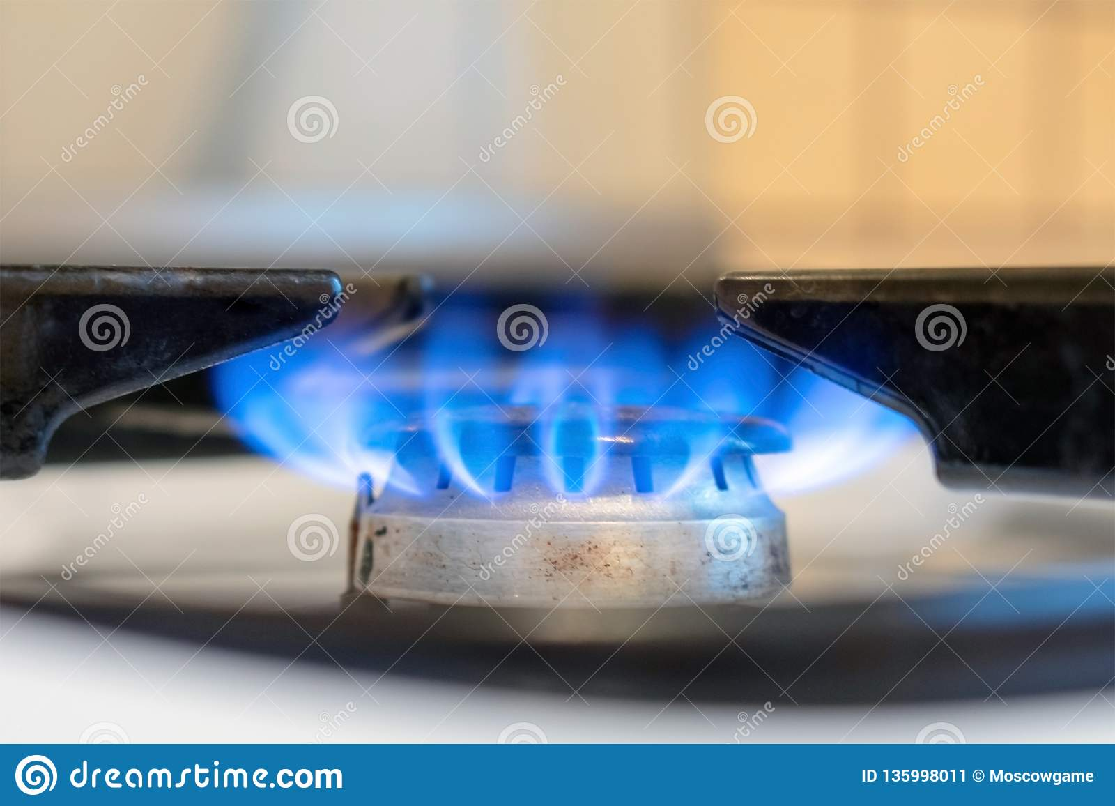 Old kitchen stove cook with blue flames burning. Can be a source of fire or explosion. Household gas stove. In kitchen room