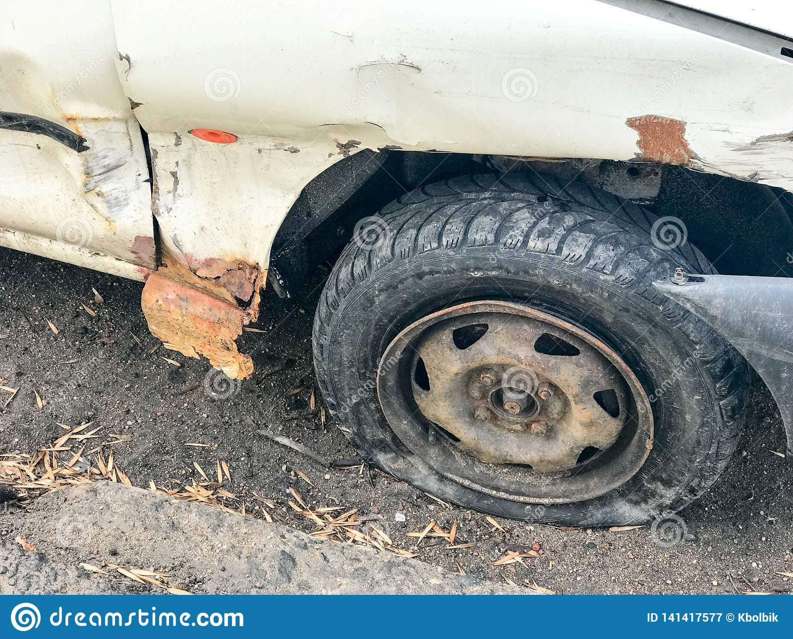 Old white rusty broken car of the carcass with lowered punctured wheels with scratches corrosion and a torn-off bumper with dents