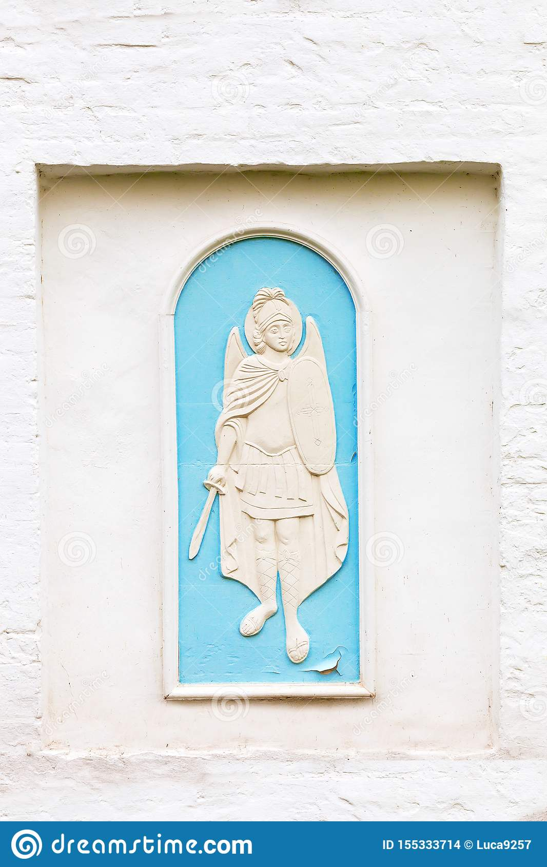 On an old white wall the relief of an angel