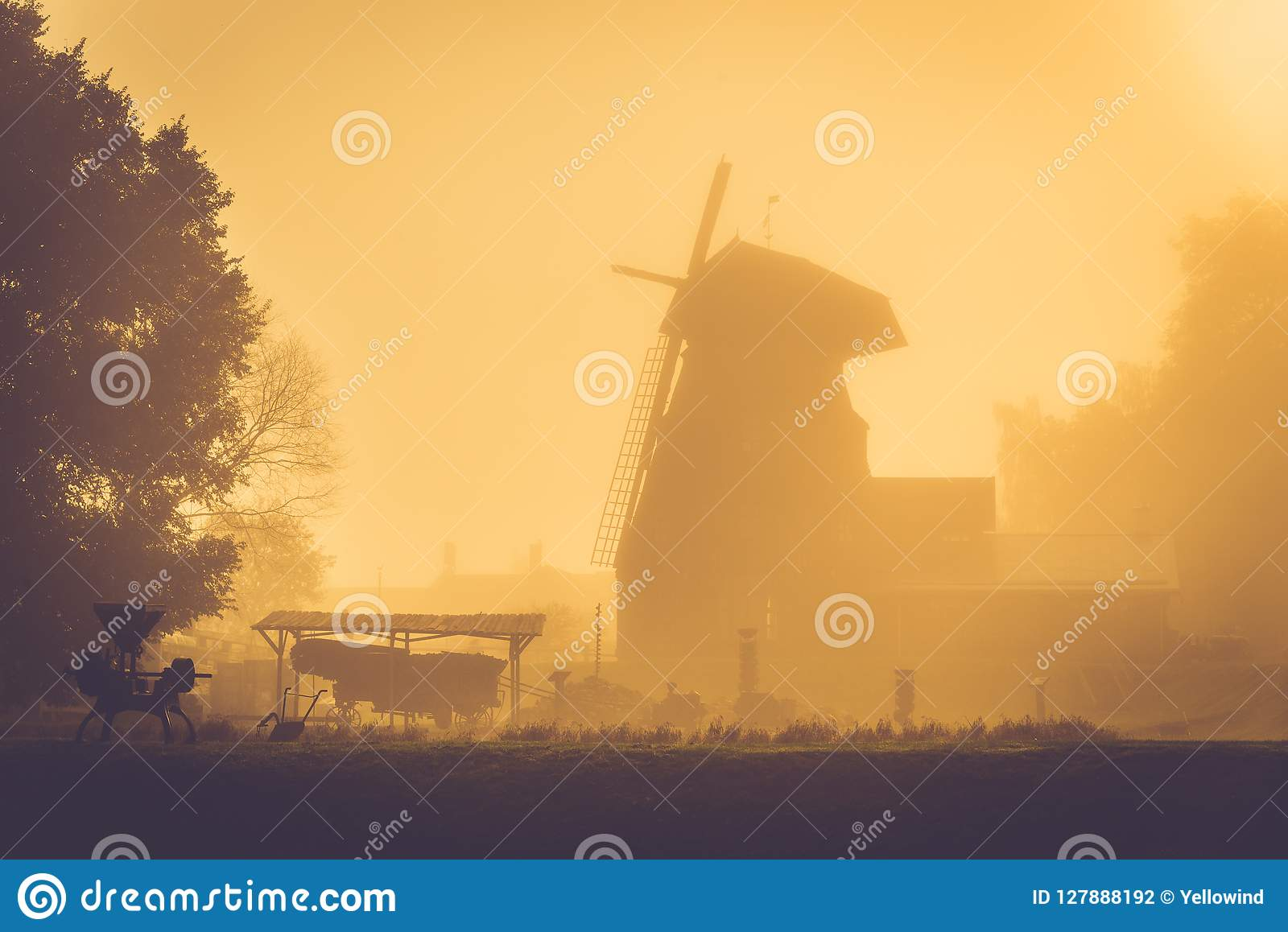 Old windmill at golden sunrise light, misty morning after rain