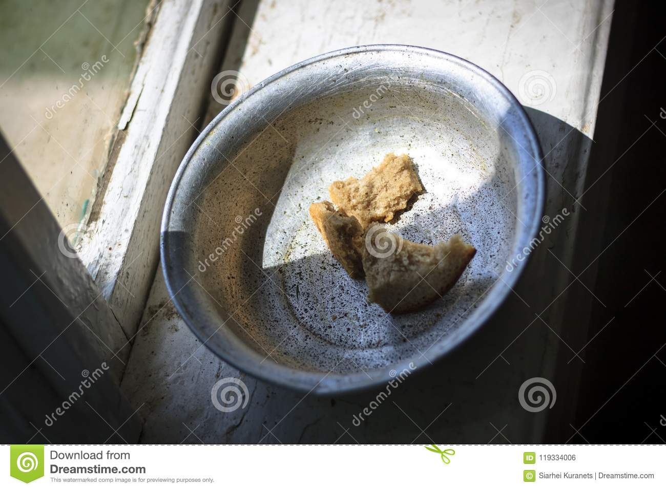The old window from it drops sunlight. On the window an old aluminum bowl in it small pieces of bread