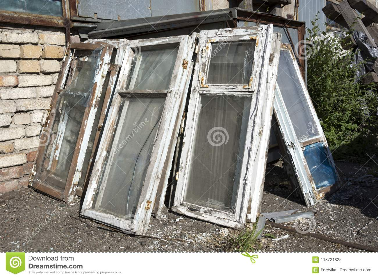The old windows in a wooden frame with shabby white paint and broken glass lie in a heap in the dump