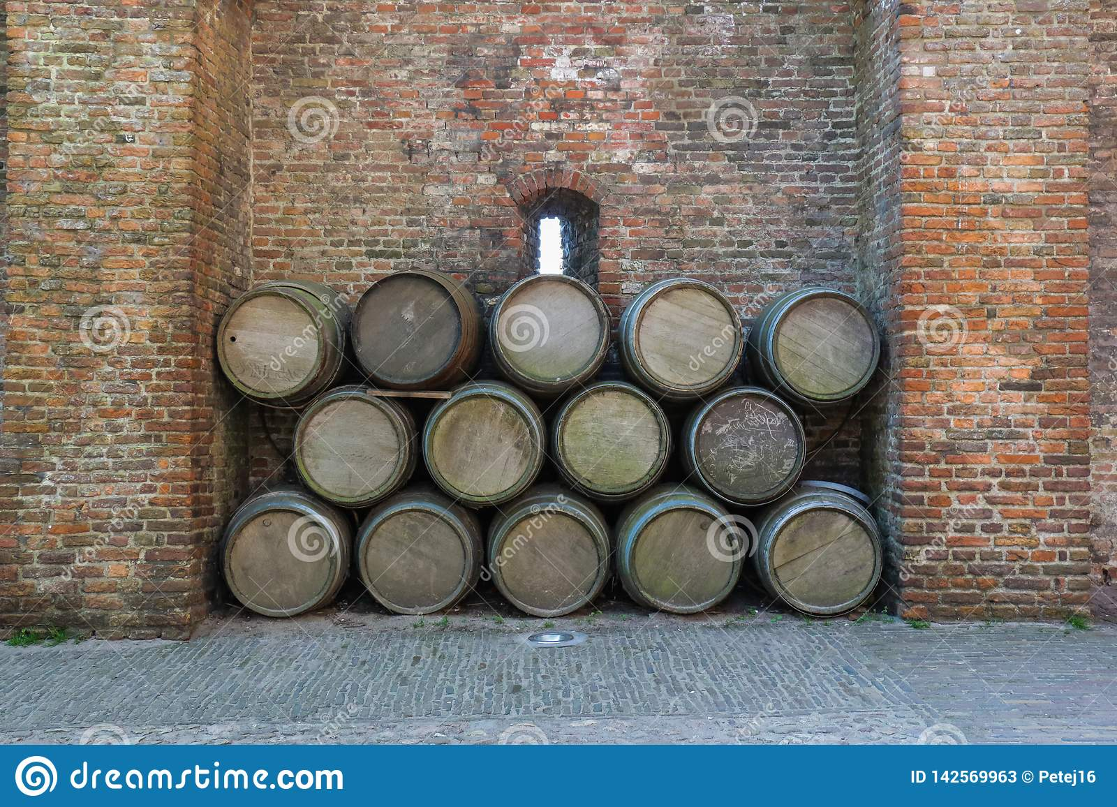 Old wine barrels stacked against a rustic brick wall
