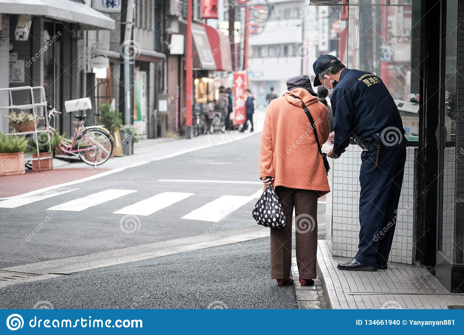 Old woman asks for direction from a police on the street of japan