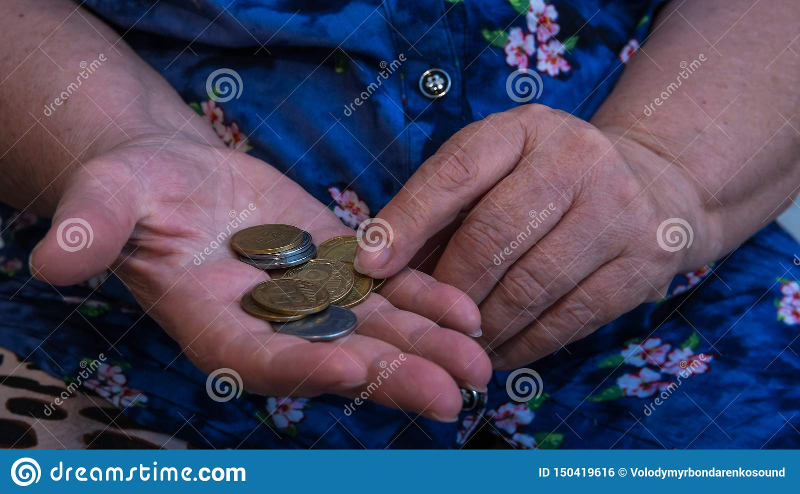 Old woman begs for alms. Closeup of money and coins in hand of poor woman
