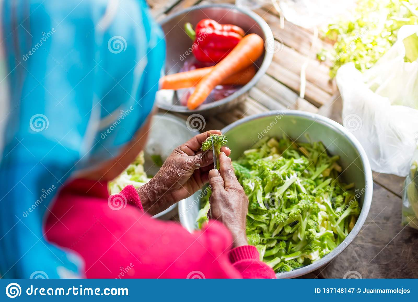 Old woman cutting vegetable in a village in Thailand